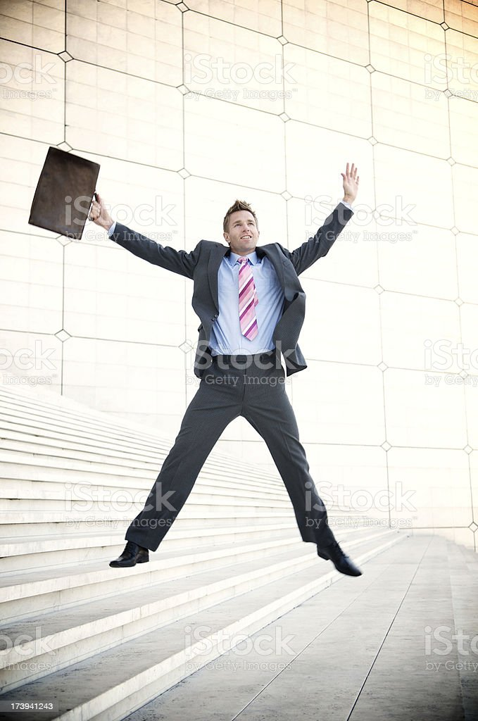 Businessman Leaps on Long Staircase stock photo