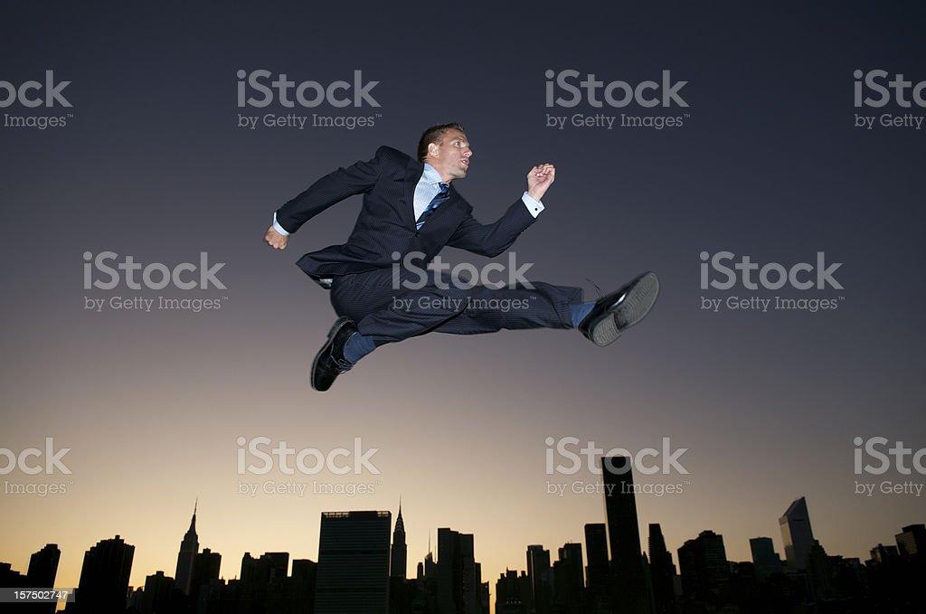 Businessman Leaps Over Sunset City Skyline Silhouette Dusk royalty-free stock photo