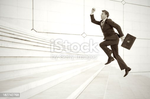 684803840istockphoto Businessman Leaps Up Long White Staircase 182742768