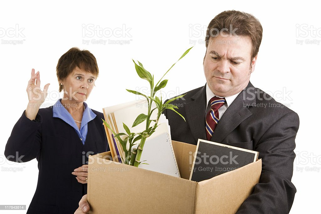 A businessman leaving work with a box full of his desk stuff White collar worker loses his job.  Sad coworker waves goodbye.  Isolated on white.   Adult Stock Photo