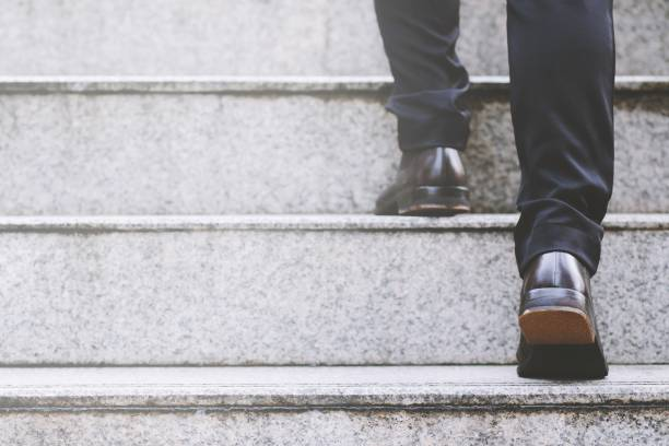 geschäftsmann beine treppensteigen in modernen stadt. - treppe stock-fotos und bilder