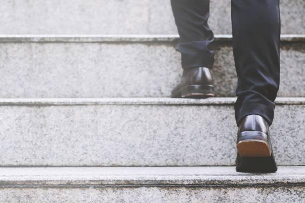zakenman benen lopen de trap in de moderne stad. - trap buiten stockfoto's en -beelden