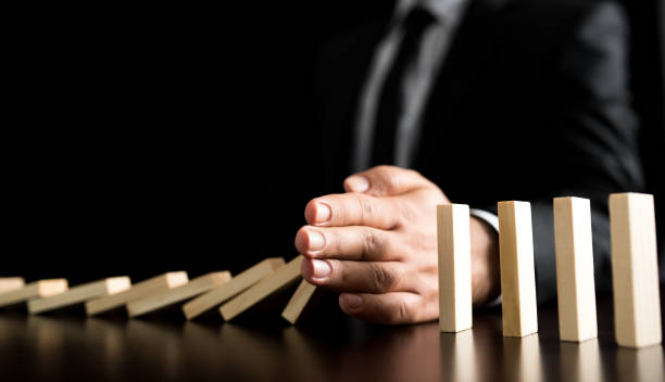 Businessman Letting Or Preventing  Dominoes Chain Toppling Chain Reaction In Business Concept, Businessman Letting Or Preventing  Dominoes Continuous Toppling On Rustic Wooden Desk boundary stock pictures, royalty-free photos & images