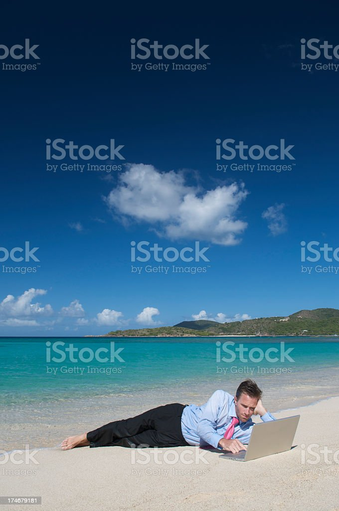 Businessman Lies Using Laptop on Tropical Beach stock photo