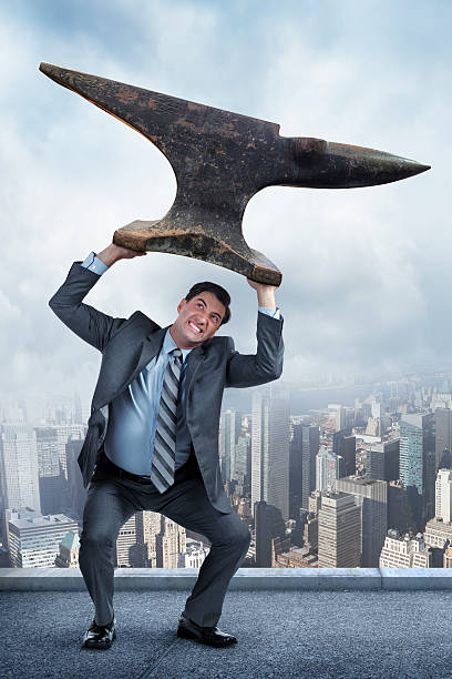 Businessman Lifting Anvil Over His Head A businessman struggling to lift a heavy anvil over his head.  A big city skyline is in the background. The businessman stands slightly above New York City on a skyscraper rooftop.  He stands crouched, attempting to keep the weight of the anvil and his professional responsibilities from crashing down and destroying what he has worked so hard to achieve.  anvil stock pictures, royalty-free photos & images