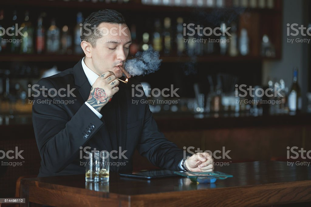 Businessman lighting his cigar stock photo