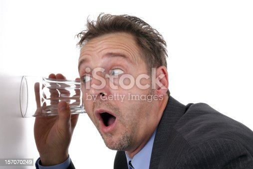 istock Businessman listening through the wall with a glass 157070249