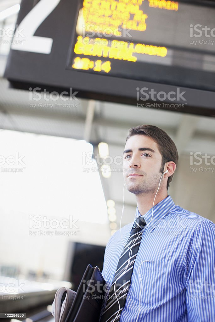 Businessman listening to music and waiting for train royalty-free stock photo