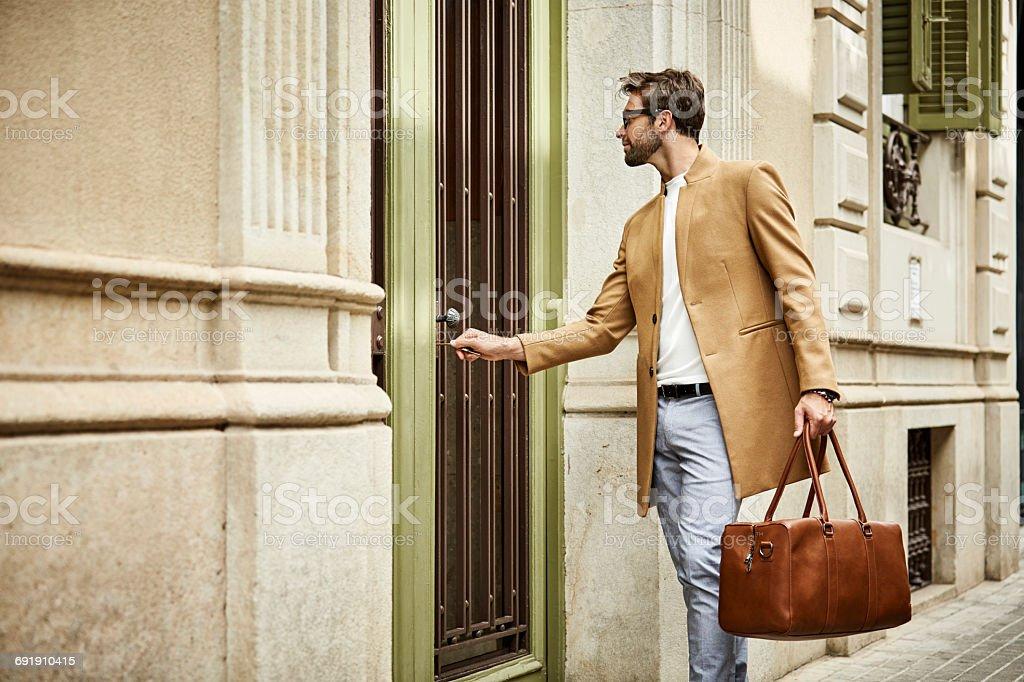 Businessman locking door at sidewalk in city - foto de acervo