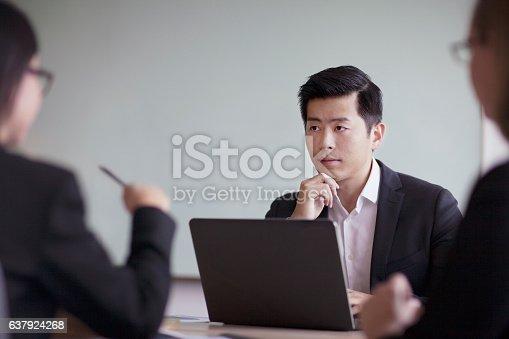 istock Businessman looking across table in office meeting 637924268