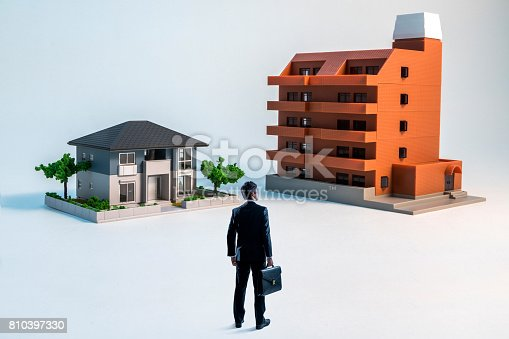 istock businessman looking at a house and a apartment building. 810397330