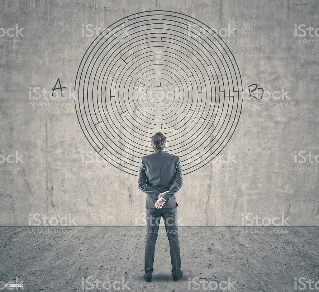Businessman looking at a maze on wall stock photo