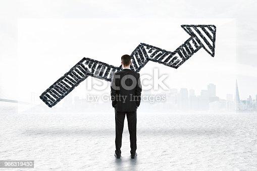 istock Businessman looking at arrow 966319430