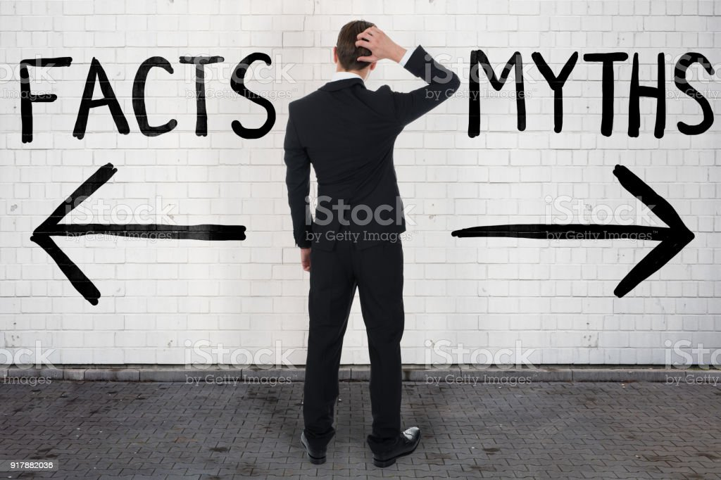 Businessman Looking At Arrow Signs Below Facts And Myths Stock Photo