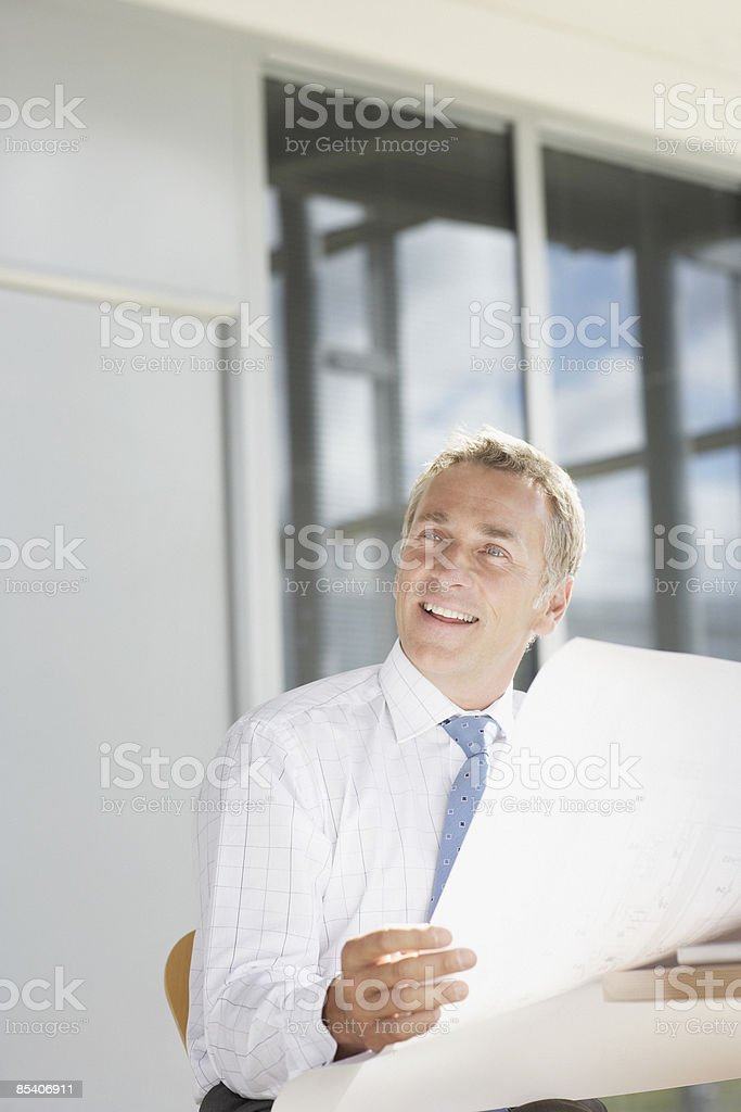 Businessman looking at blueprints royalty-free stock photo