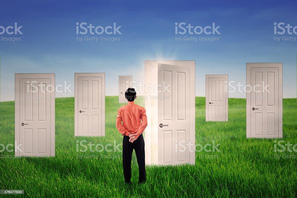 Businessman looking at bright door stock photo