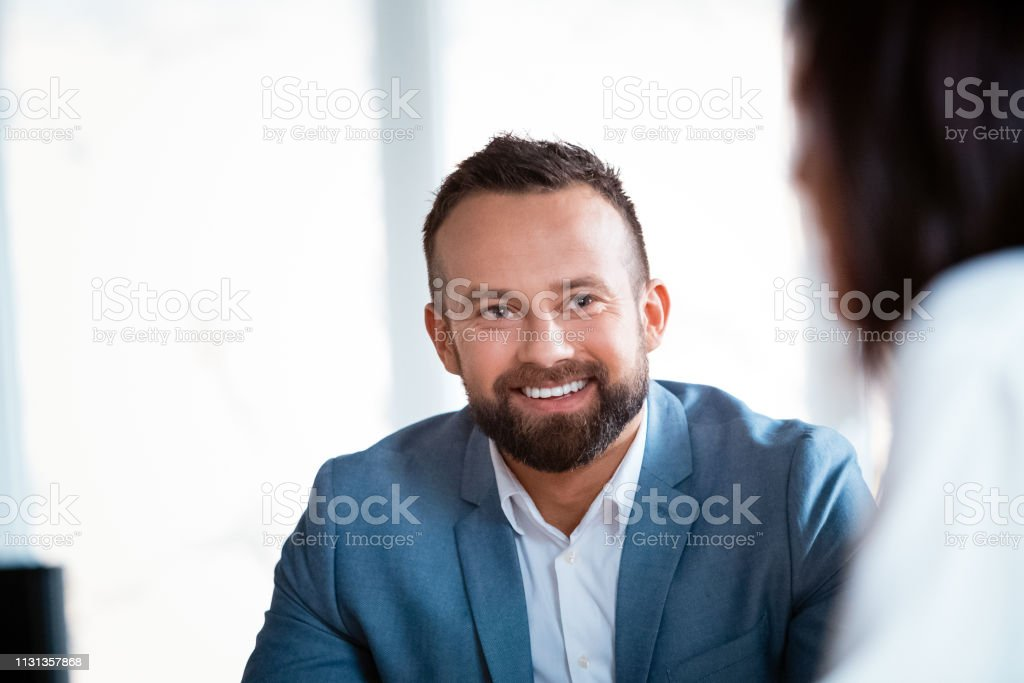 Businessman looking at businesswoman in office Smiling businessman looking at businesswoman during meeting. Male and female design professionals are at creative workplace. They are planning at office. 30-39 Years Stock Photo