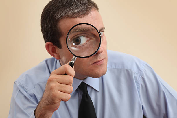 Businessman looking at camera through a magnifying glass Businessman looking through magnifying glass. Focus on his hand and magnifying glass. microscopic image stock pictures, royalty-free photos & images