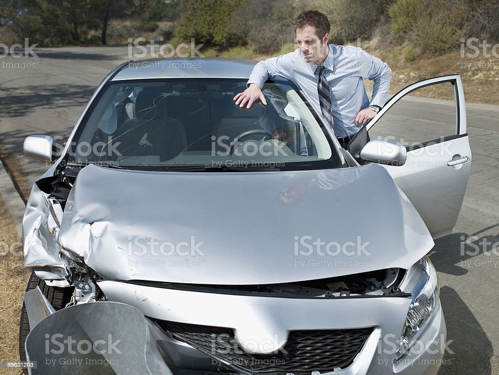Businessman looking at car accident damage foto
