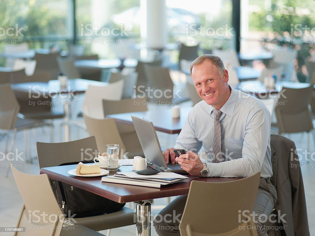 Businessman looking at cell phone in cafeteria royalty-free stock photo