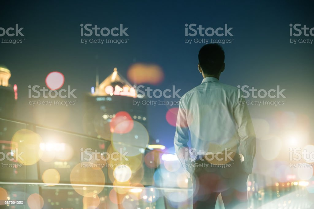 Businessman looking at city at night stock photo