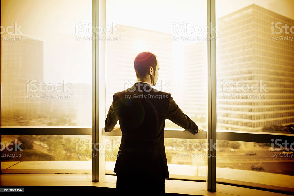 Businessman looking at city from office window stock photo