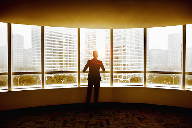 Businessman looking at city in modern office - Photo