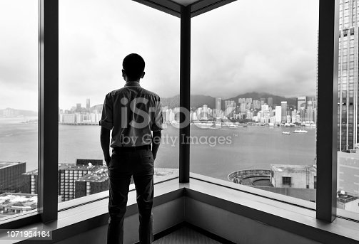 Businessman looking at city through office window.