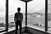 Businessman looking at city through office window