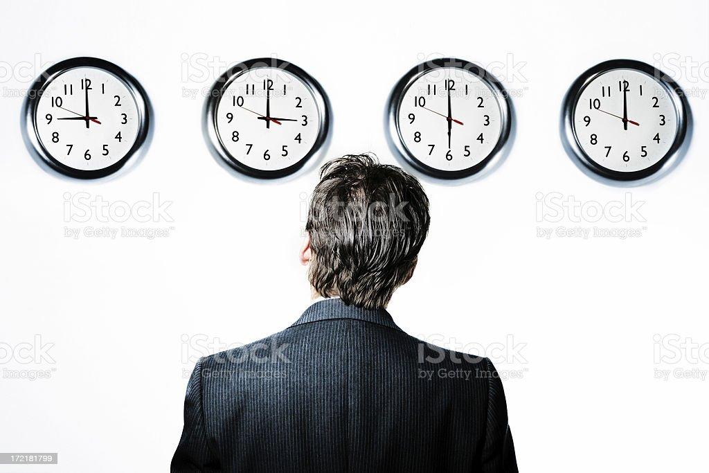 Businessman looking at clocks stock photo