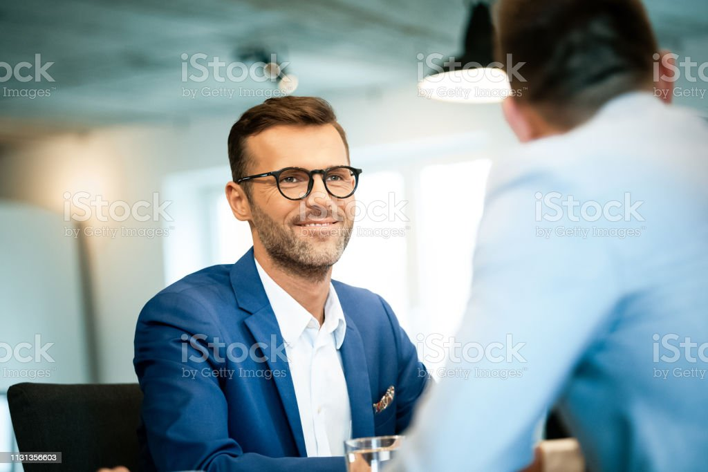 Businessman looking at colleague during meeting Smiling businessman looking at colleague during meeting in creative workplace. Male professionals are working at office. They are planning strategy. 30-39 Years Stock Photo