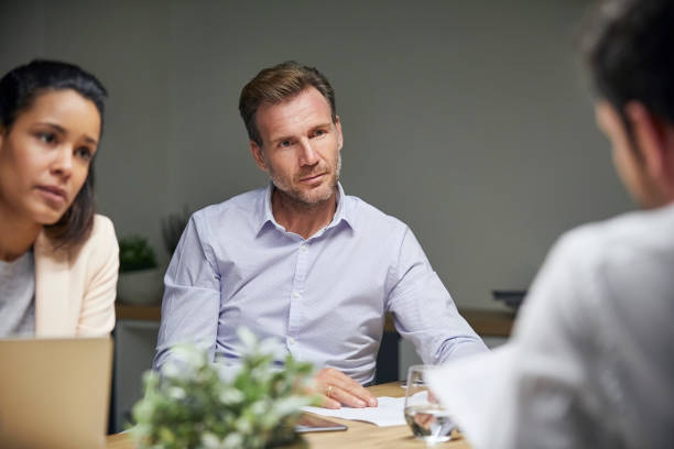 Businessman looking at coworker in textile factory stock photo