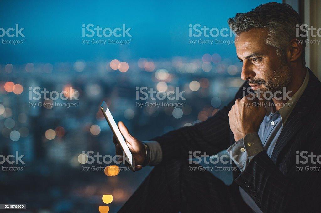 Businessman looking at digital tablet at night - Lizenzfrei Abenddämmerung Stock-Foto