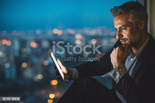 istock Businessman looking at digital tablet at night 624978806