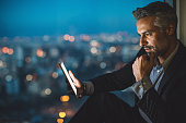 Businessman sitting on a windowsill at night and looking at a digital tablet, with cityscape at the background and copy space.