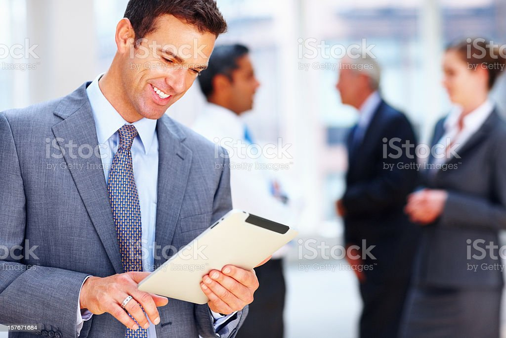 Businessman looking at document with team in the background royalty-free stock photo
