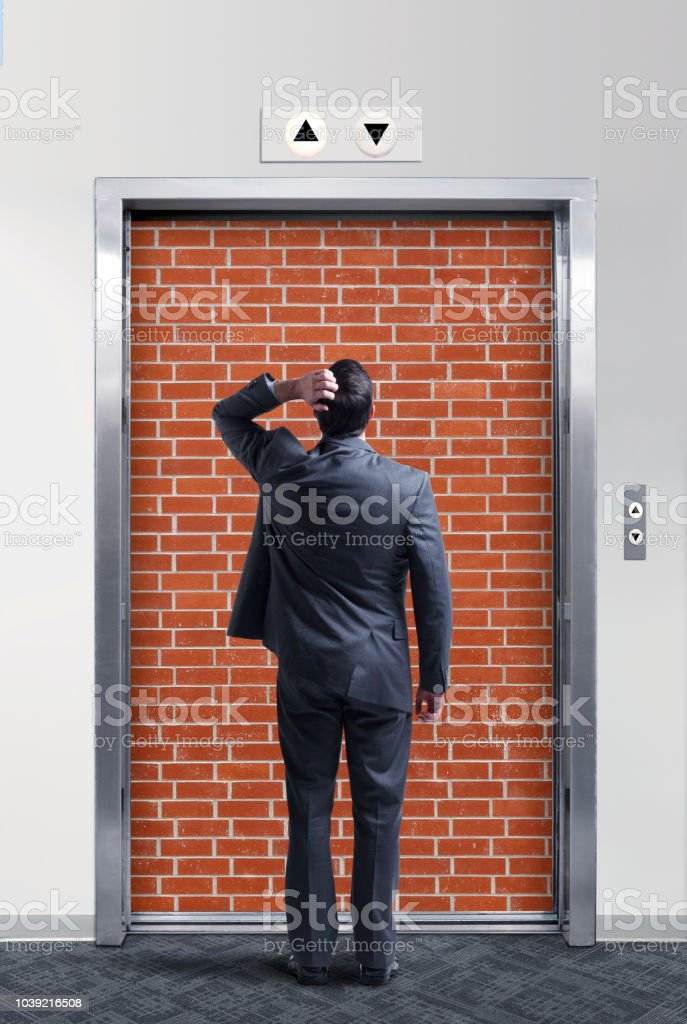 Businessman Looking At Elevator Blocked By Brick Wall stock photo