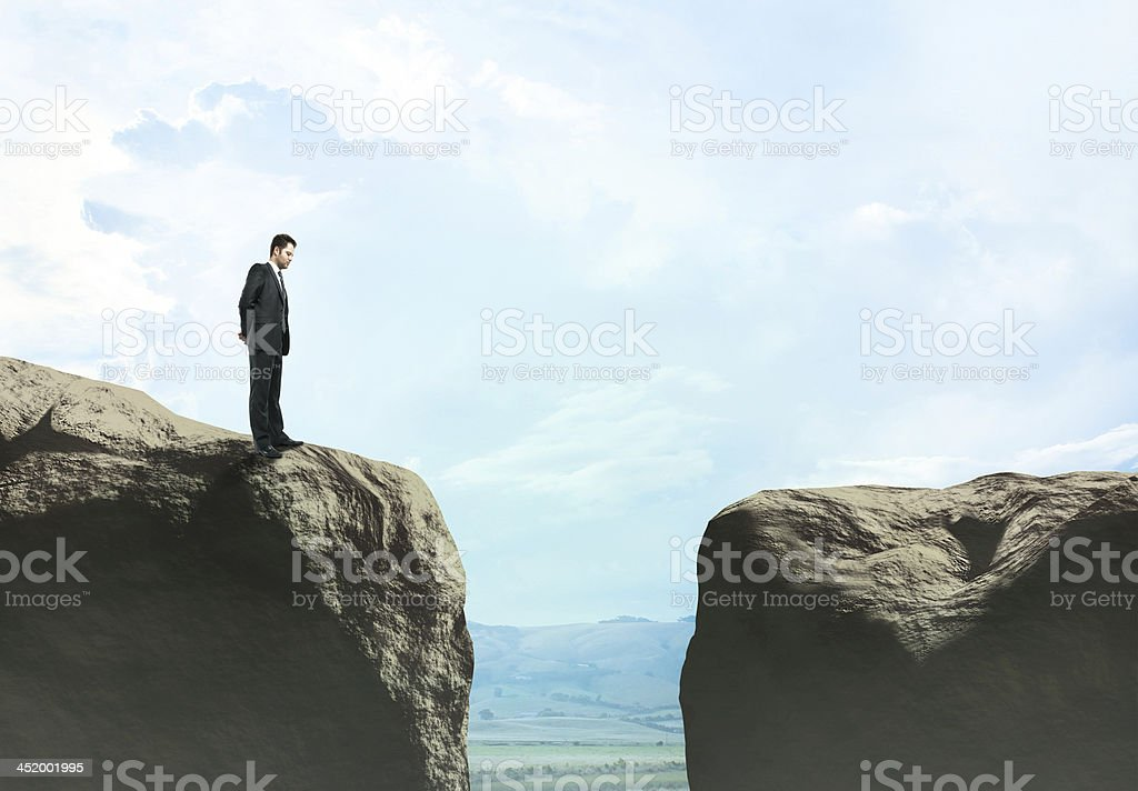 Businessman looking at gap between two cliffs stock photo