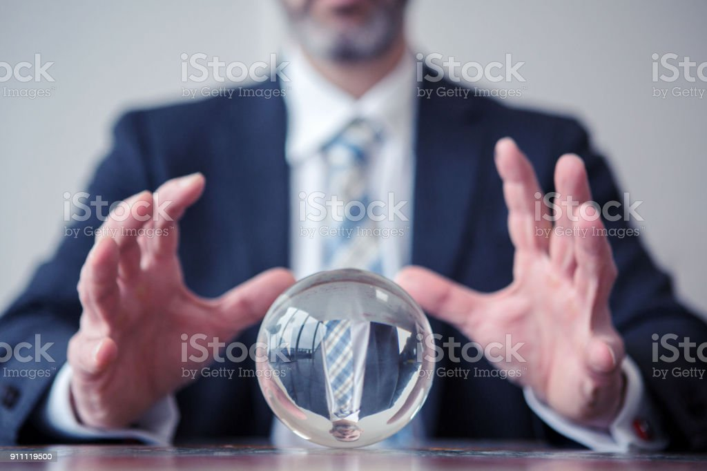 businessman looking at glass ball on table stock photo