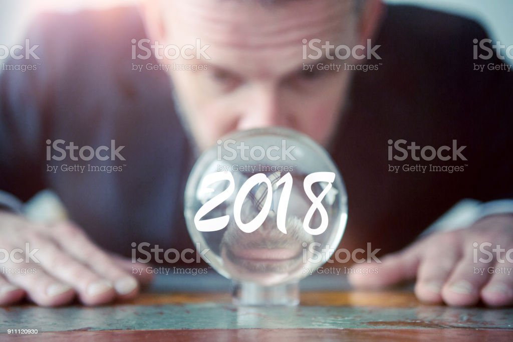businessman looking at glass ball with the number 2018 stock photo