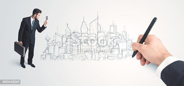 istock Businessman looking at hand drawn city on wall 940443342