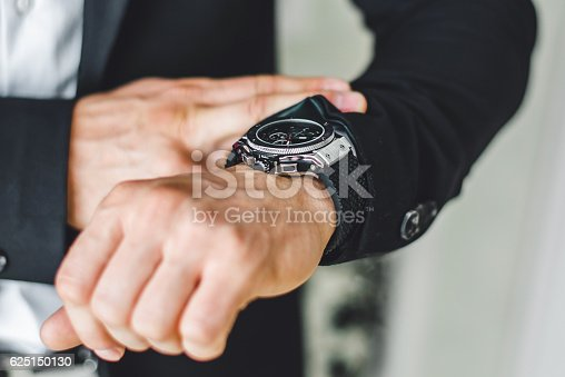 istock businessman looking at his watch. 625150130