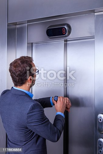 638591126 istock photo Businessman looking at his watch while waiting for the elevator 1178836854
