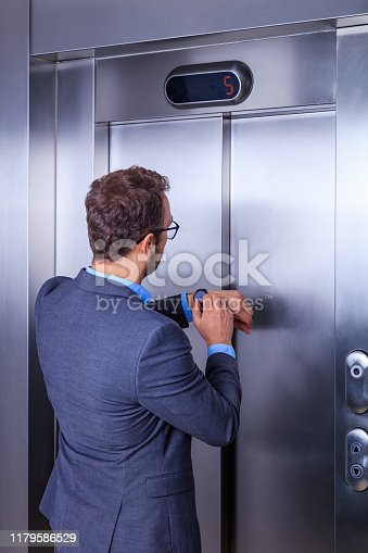 638591126 istock photo Businessman looking at his watch while waiting for the elevator 1179586529