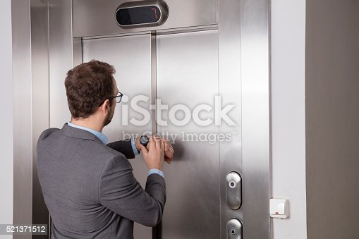 638591126 istock photo Businessman looking at his watch while waiting for the elevator 521371512