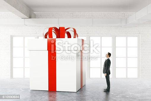 istock Businessman looking at huge present 610990634