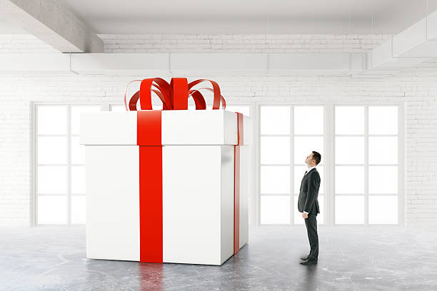 Businessman looking at huge present stock photo