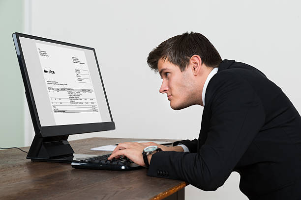 Businessman Looking At Invoice On Computer Young Businessman Looking At Invoice On Computer Screen In Office bad posture stock pictures, royalty-free photos & images