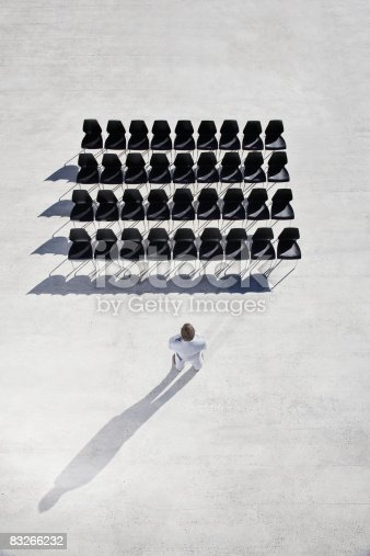 istock Businessman looking at lines of empty office chairs 83266232