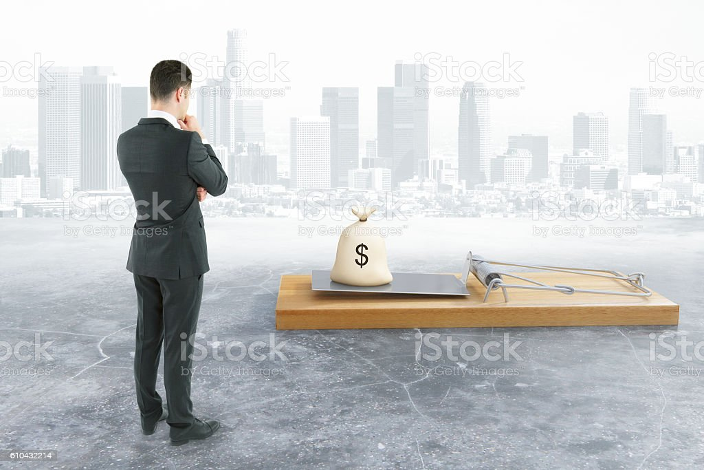 Businessman looking at mousetrap with money stock photo